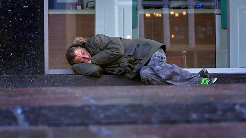 A homeless man sleeping on a pavement.