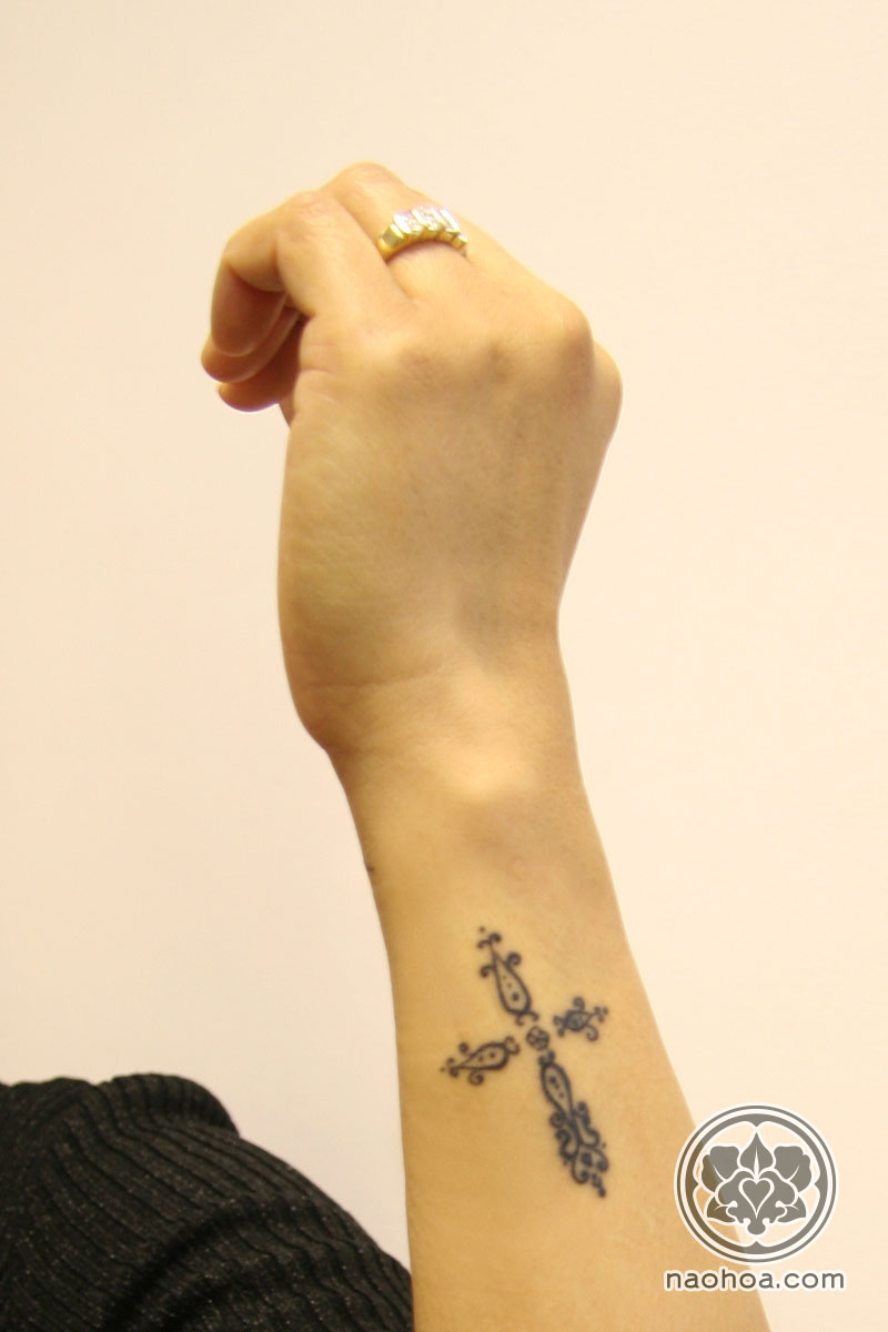 A small, intricate tattoo of a Christian cross on a woman's arm.
