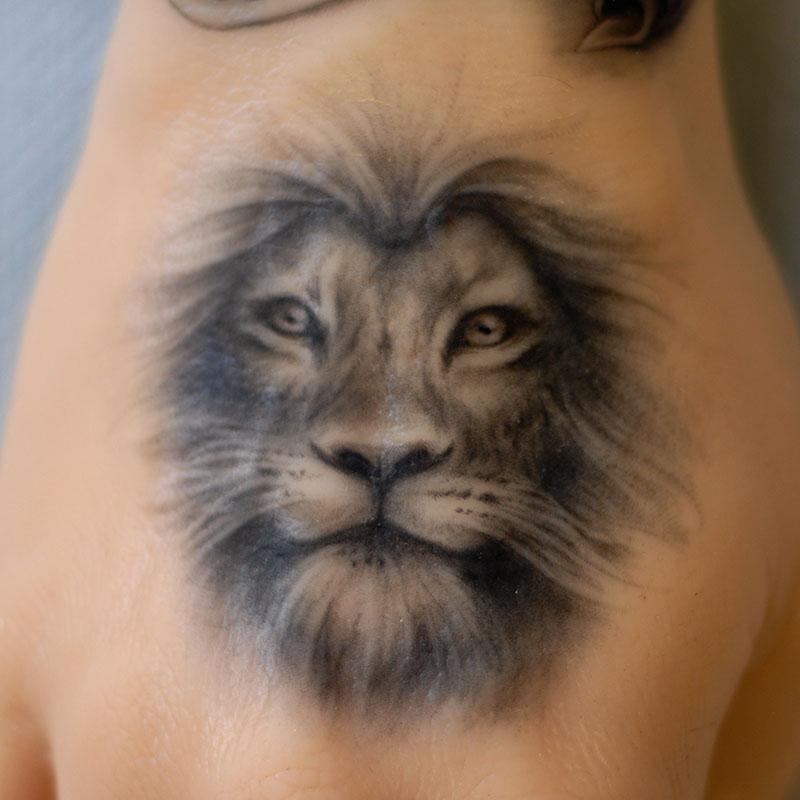 Realistic black and white lion tattoo on a Pound of Flesh arm by Naomi Hoang, NAOHOA Luxury Bespoke Tattoos, Cardiff, Wales (UK).