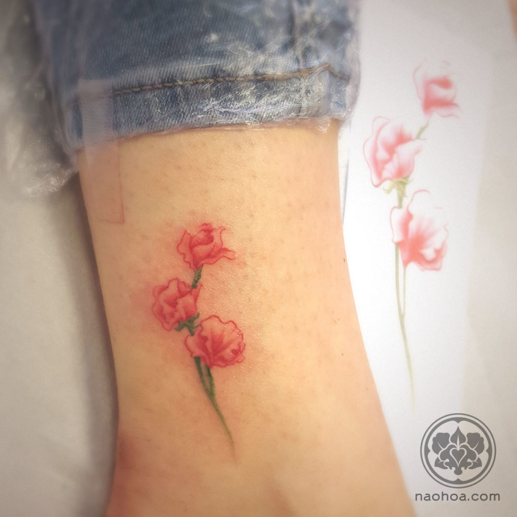 Photograph of a custom-designed tattoo of a sweetpea flower, by Naomi Hoang at NAOHOA Luxury Bespoke Tattoos, City Road, Cardiff (Wales, UK).