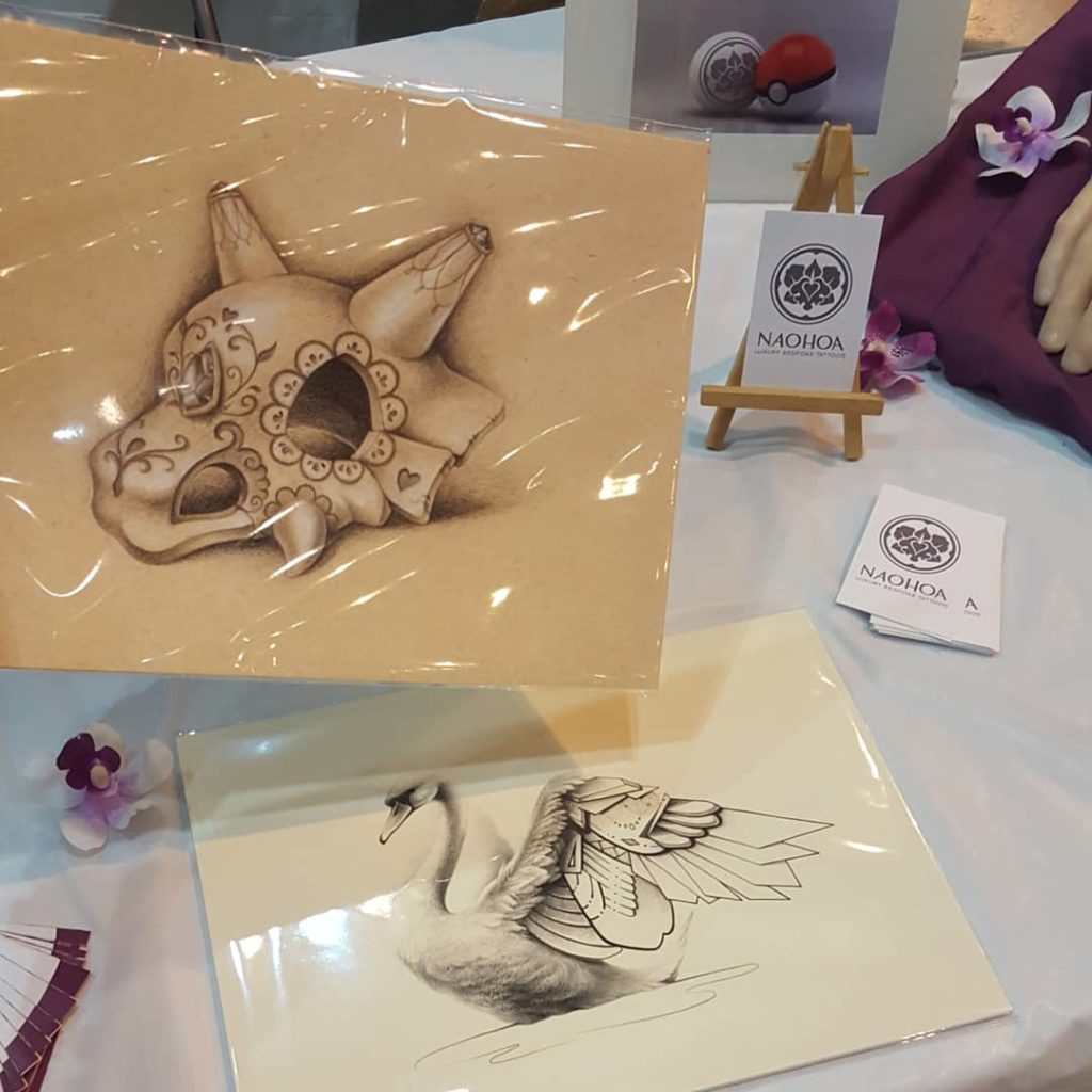 NAOHOA Luxury Bespoke Tattoos at Cardiff Comic Con, selling Sugarskull Cubone and Geo Swan Art Prints by Naomi Hoang.