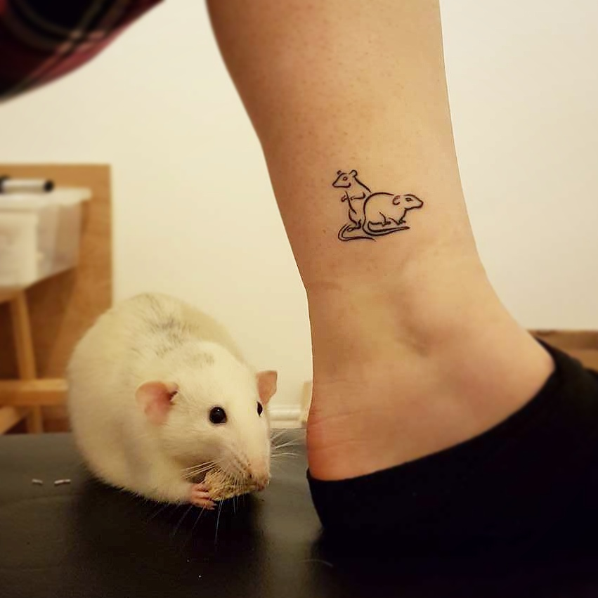 Photo of an ankle tattoo of two rats next to the woman's pet rat. Designed and tattooed by Naomi Hoang at NAOHOA Luxury Bespoke Tattoos, Cardiff, Wales, UK.