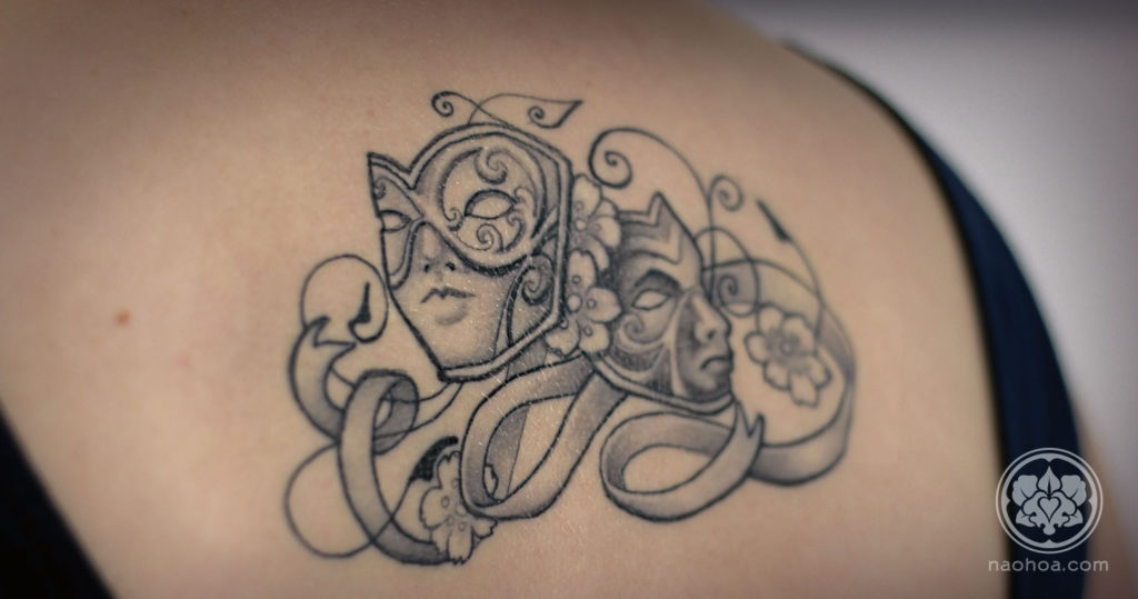 Black and white tattoo of two theatre masks, surrounded by flowers and swirling ribbons.