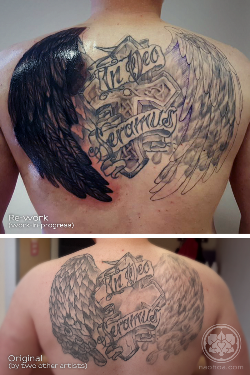 """A work-in-progress shot of a large back tattoo containing a Christian cross, a pair of wings and the saying, """"In dec seramus""""."""